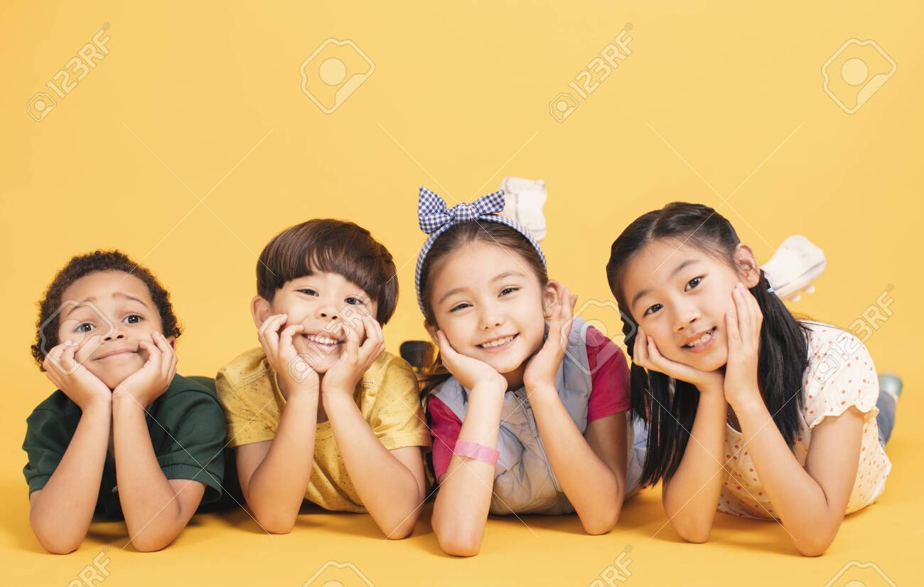 Happy children lying together on ground - 134003699