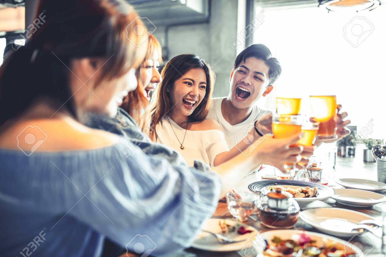 happy young friends dining and drinking beer at restaurant - 143175664