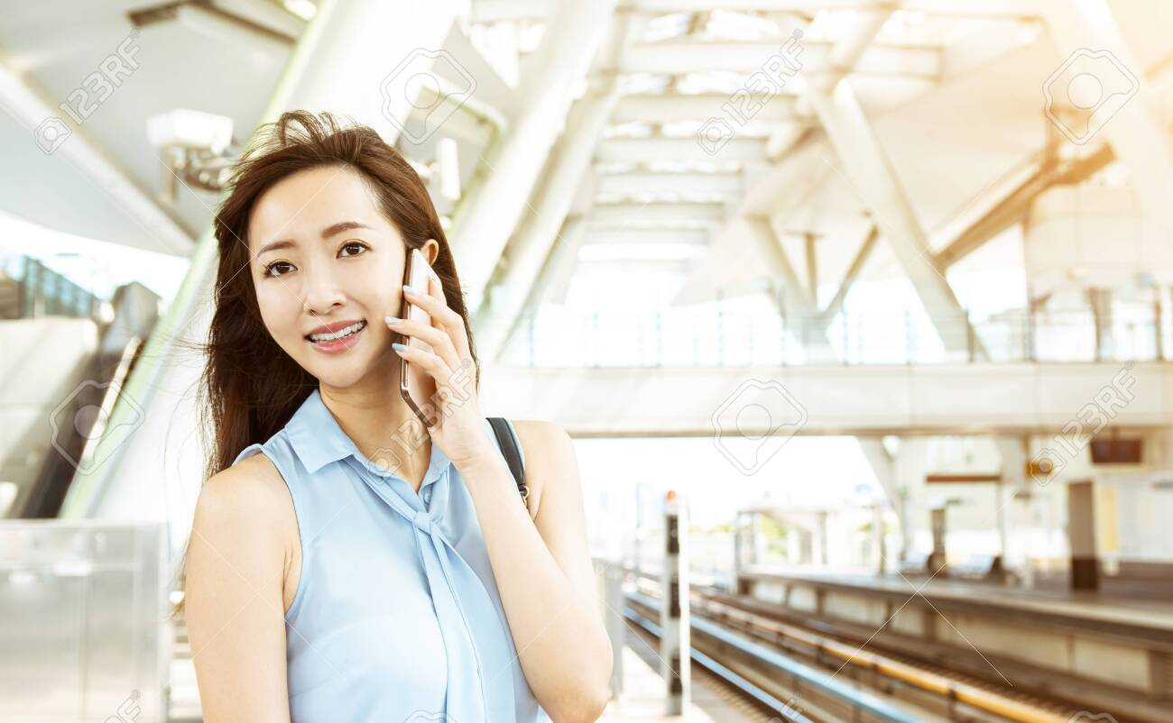 young woman talking on the phone in train station - 150831667