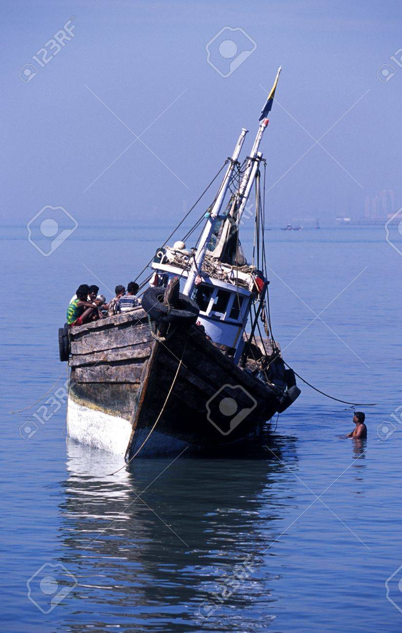 Native Indian fishing boat with a group of fishermen on board moored in shallow chest high water listing heavily to one side Stock Photo - 19710975