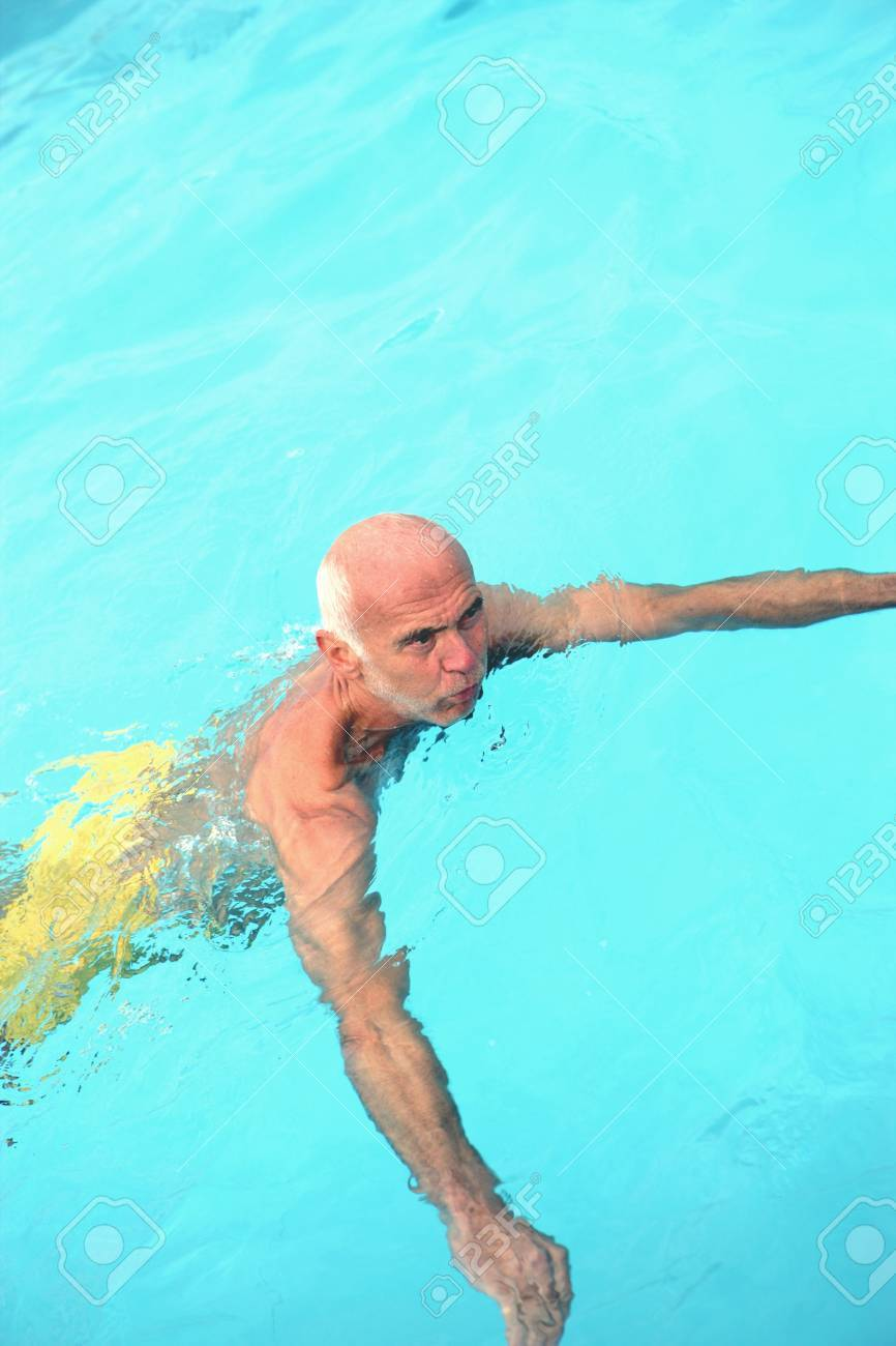 Senior man having a refreshing swim in a turquoise blue pool in a healthy lifestyle concept Stock Photo - 19723979