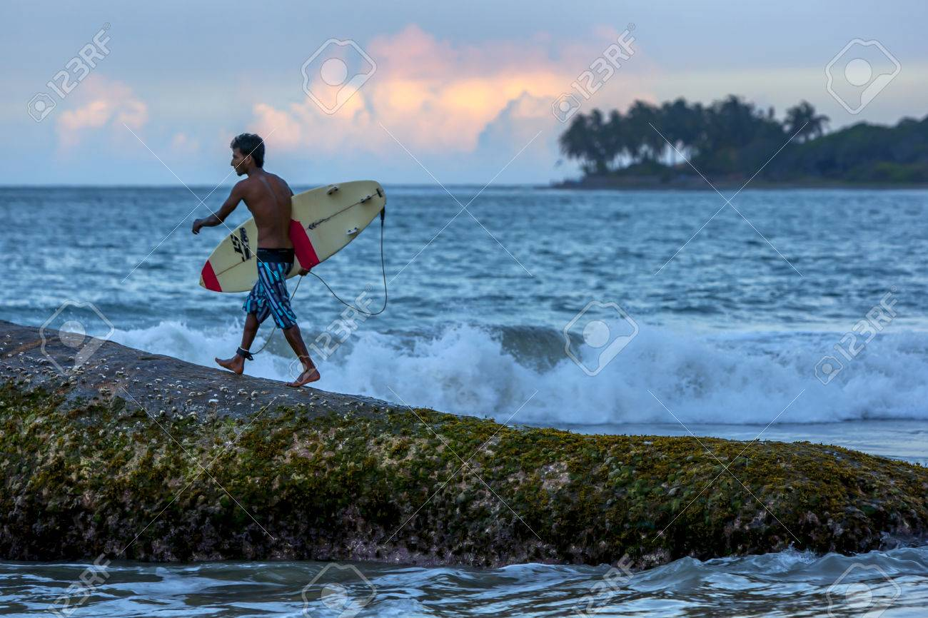 A surfer prepares to jump off Eight Star Rock to surf a beach break in the late afternoon at Arugan Bay in Sri Lanka. - 52857221