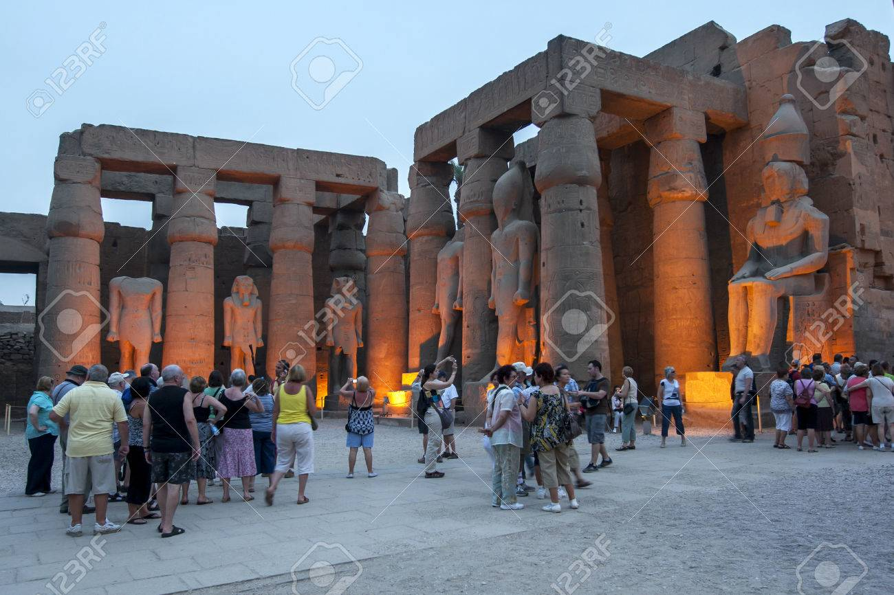 the sun sets over the courtyard of ramesses ll at the luxor temple
