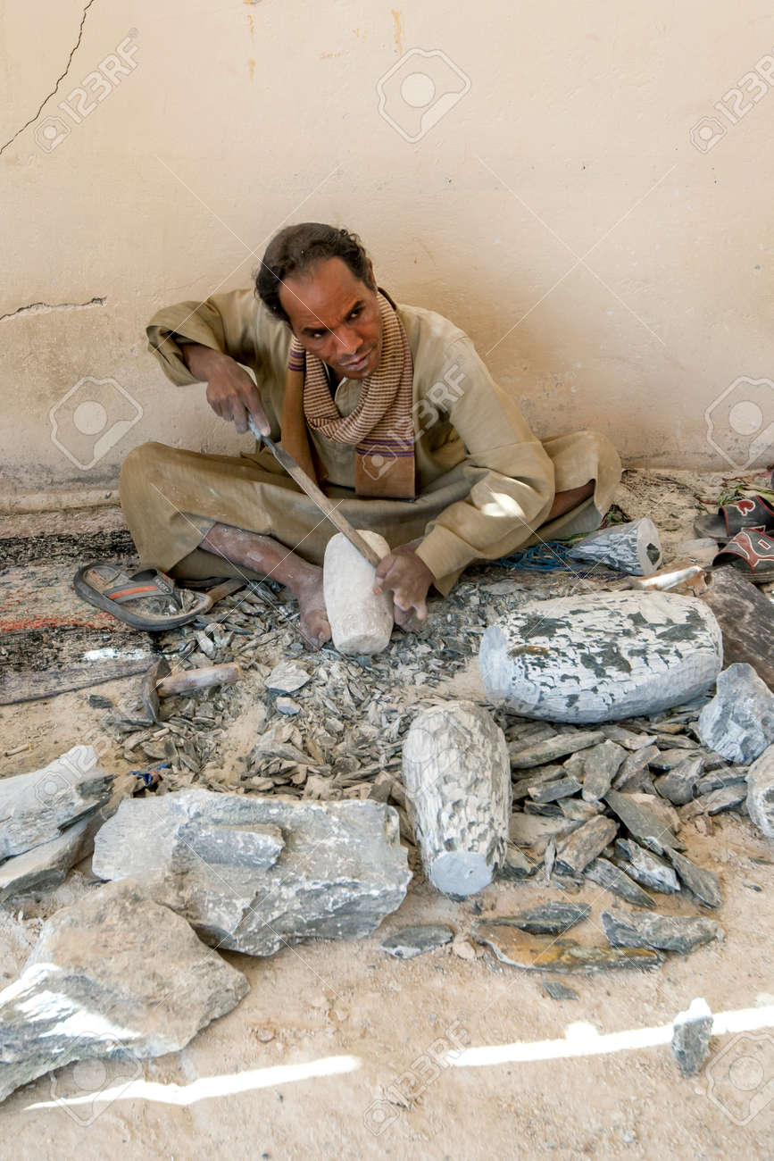 A man shapes a piece of stone using a metal file at an alabaster factory at Luxor in Egypt. - 172089032