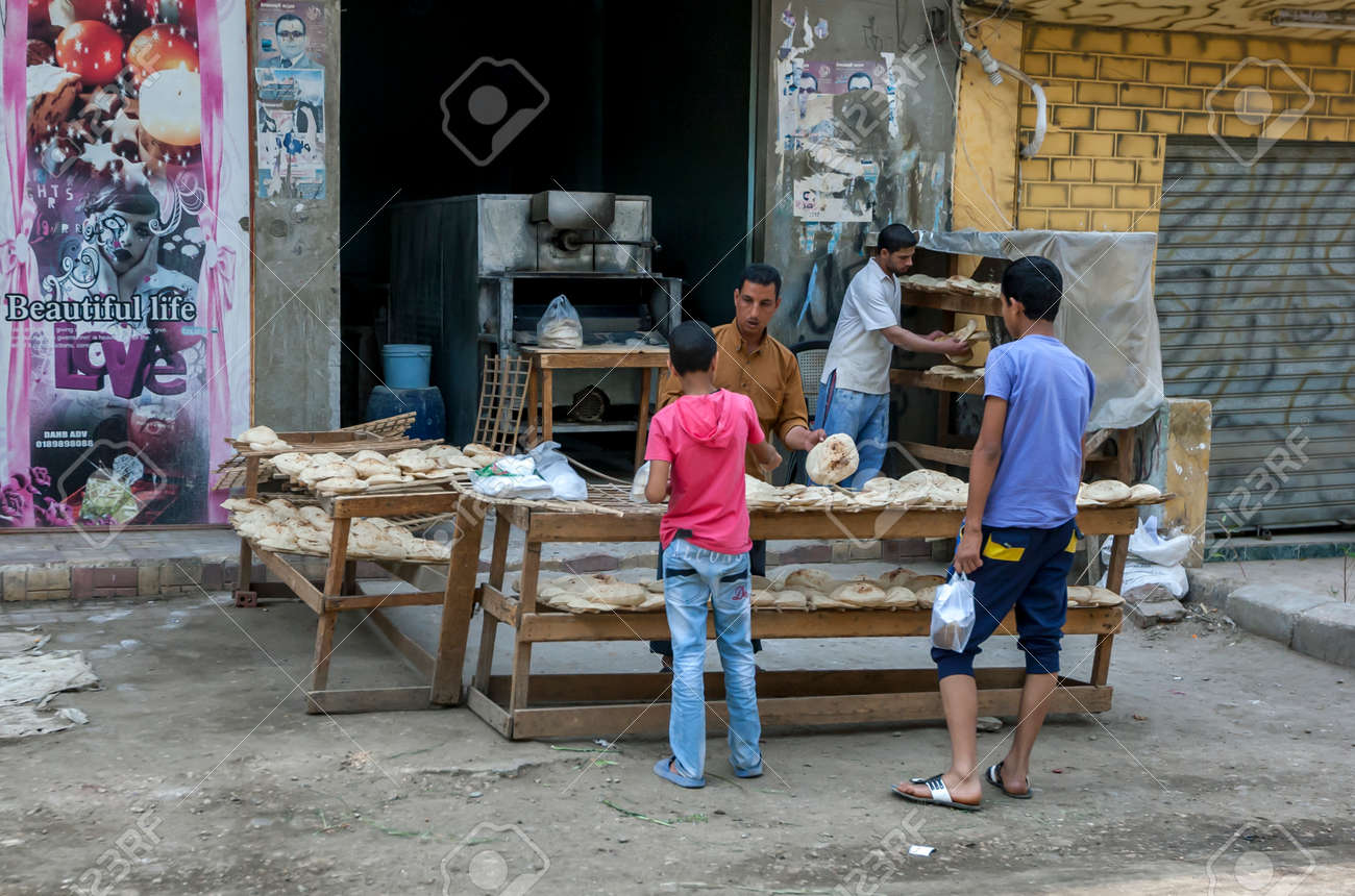 A man selling flat bread to a customer from a bakery on the outskirts of Cairo in Egypt. - 172089026