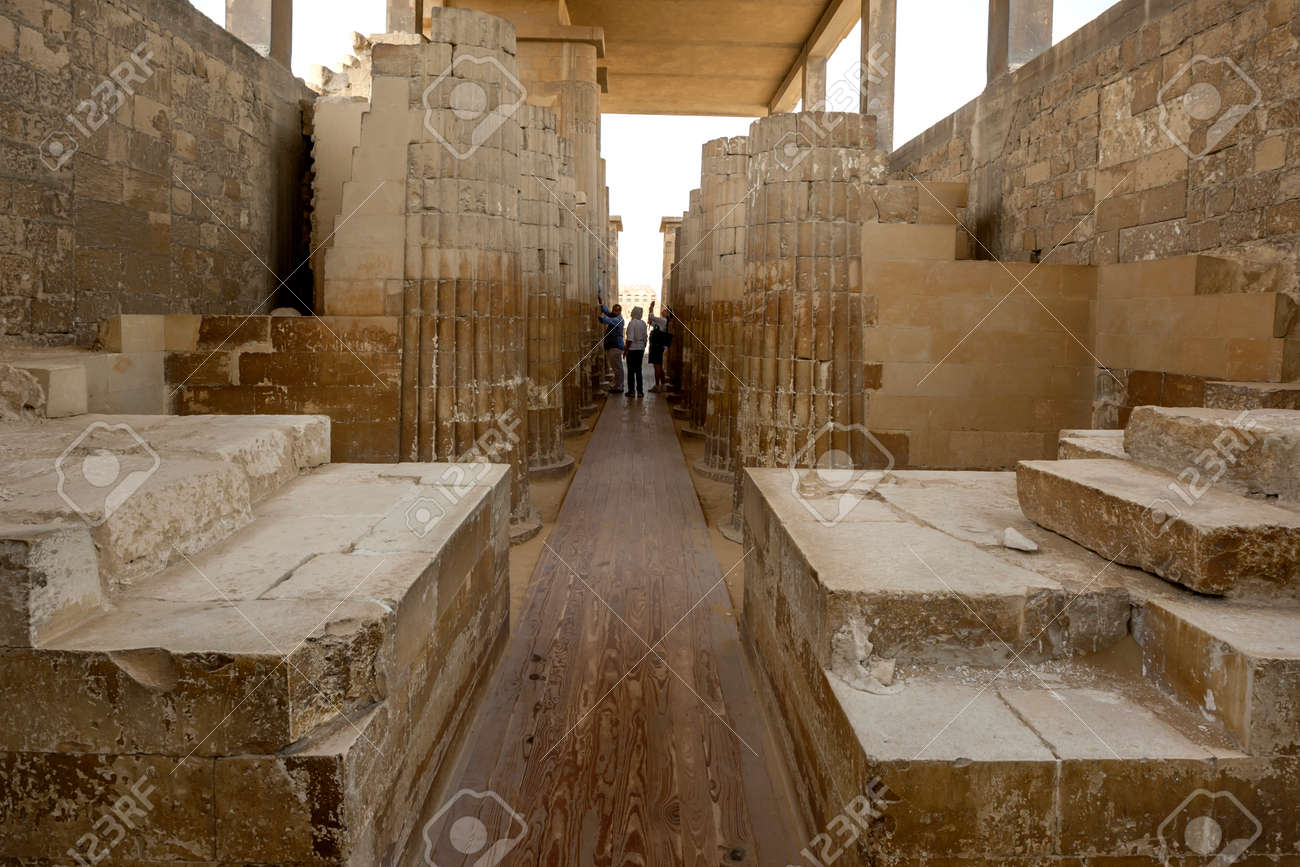 Tourists admire the stone carved columns of the Hypostyle Hall at the entrance to the Step Pyramid (Pyramid of Djoser) at Saqqara in northern Egypt. - 172089020