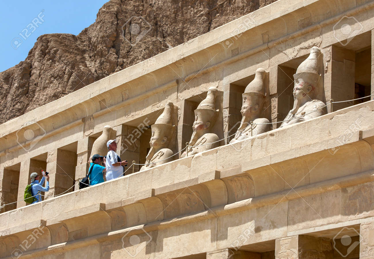 Tourists admire and photograph the row of Osiris pillars which stand along the upper terrace at the Mortuary Temple of Hatshepsut at Deir al-Bahri near Luxor in central Egypt. - 172089019