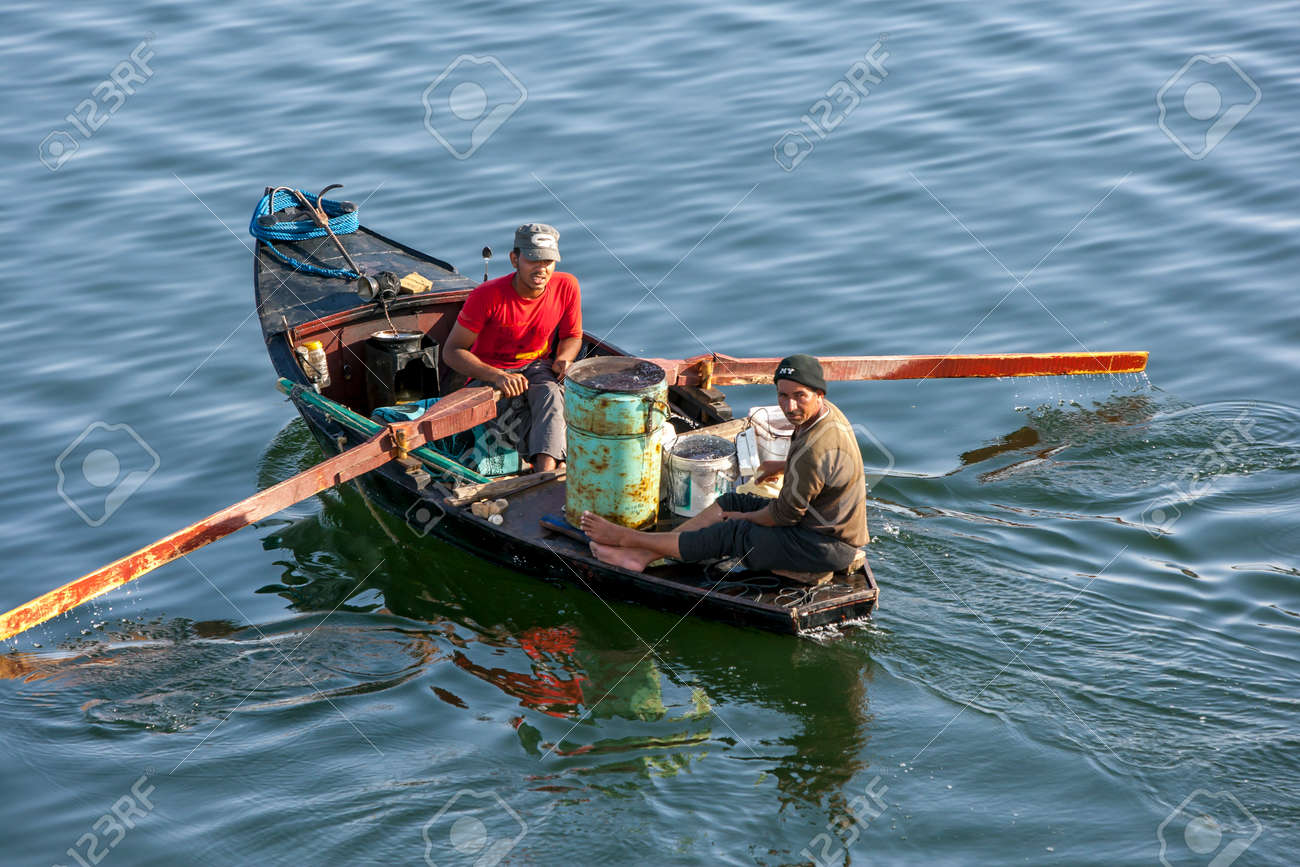Egyptian men row their boat on the River Nile adjacent to the Esna Lock in central Egypt. - 173508731