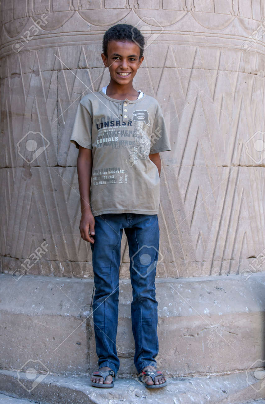 A smiling Egyptian boy stands in front of a giant stone column at the Temple of Horus at Edfu in central Egypt. - 173508735