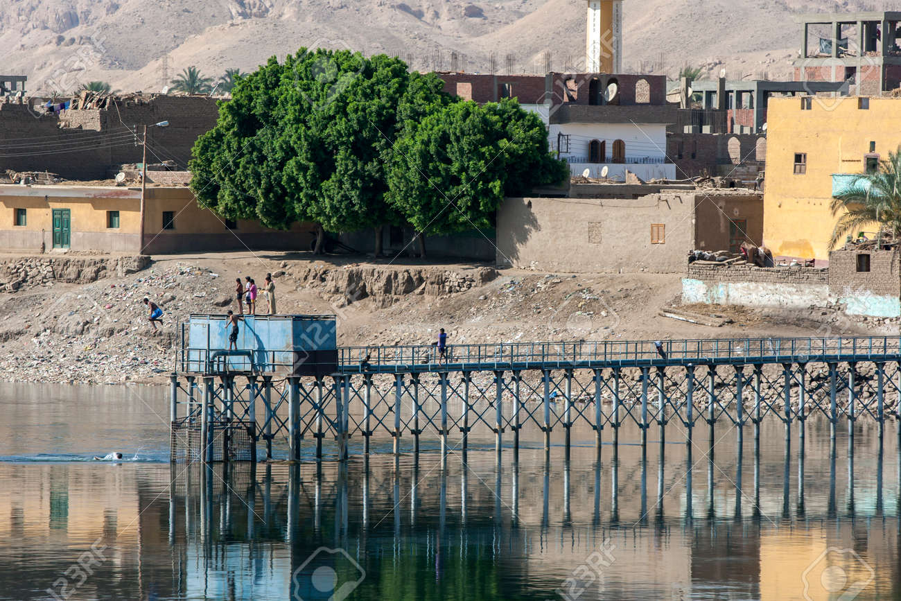 A man jumps from a water pumping station into the River Nile north of Esna in the afternoon. - 173508741