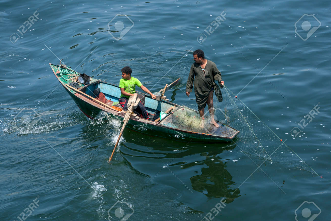Fishermen in a rowing boat pull in their net on a section of the River Nile south of Luxor in central Egypt. - 173508745