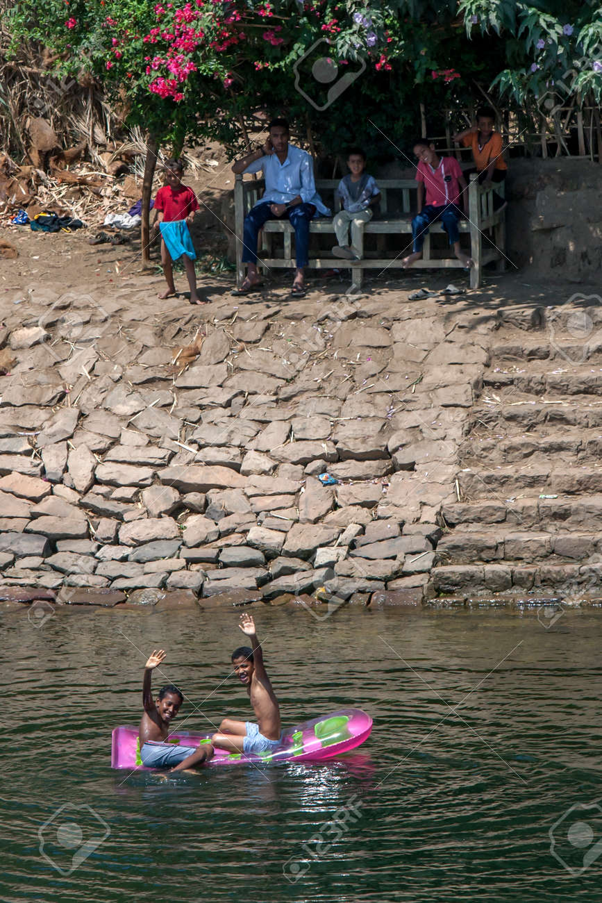 Egyptian boys play on an inflatable boat in the River Nile at Edfu in Egypt on a hot day. - 173509884