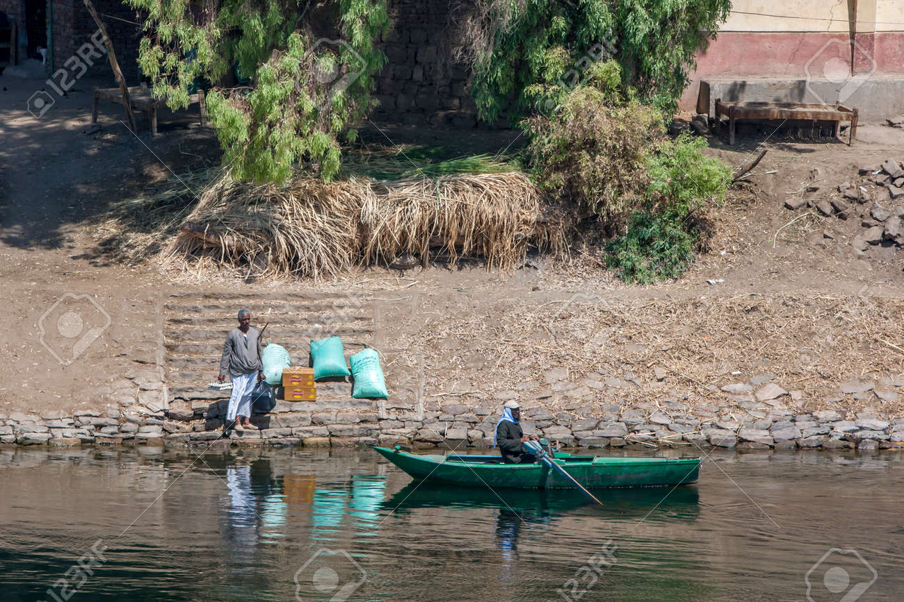 A man waits on the bank of the River Nile with food supplies to be picked up by a rowing boat south of Edfu in central Egypt. - 173509881