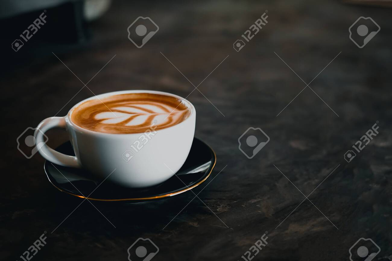 Coffee cup with latte art on old table - 144212992