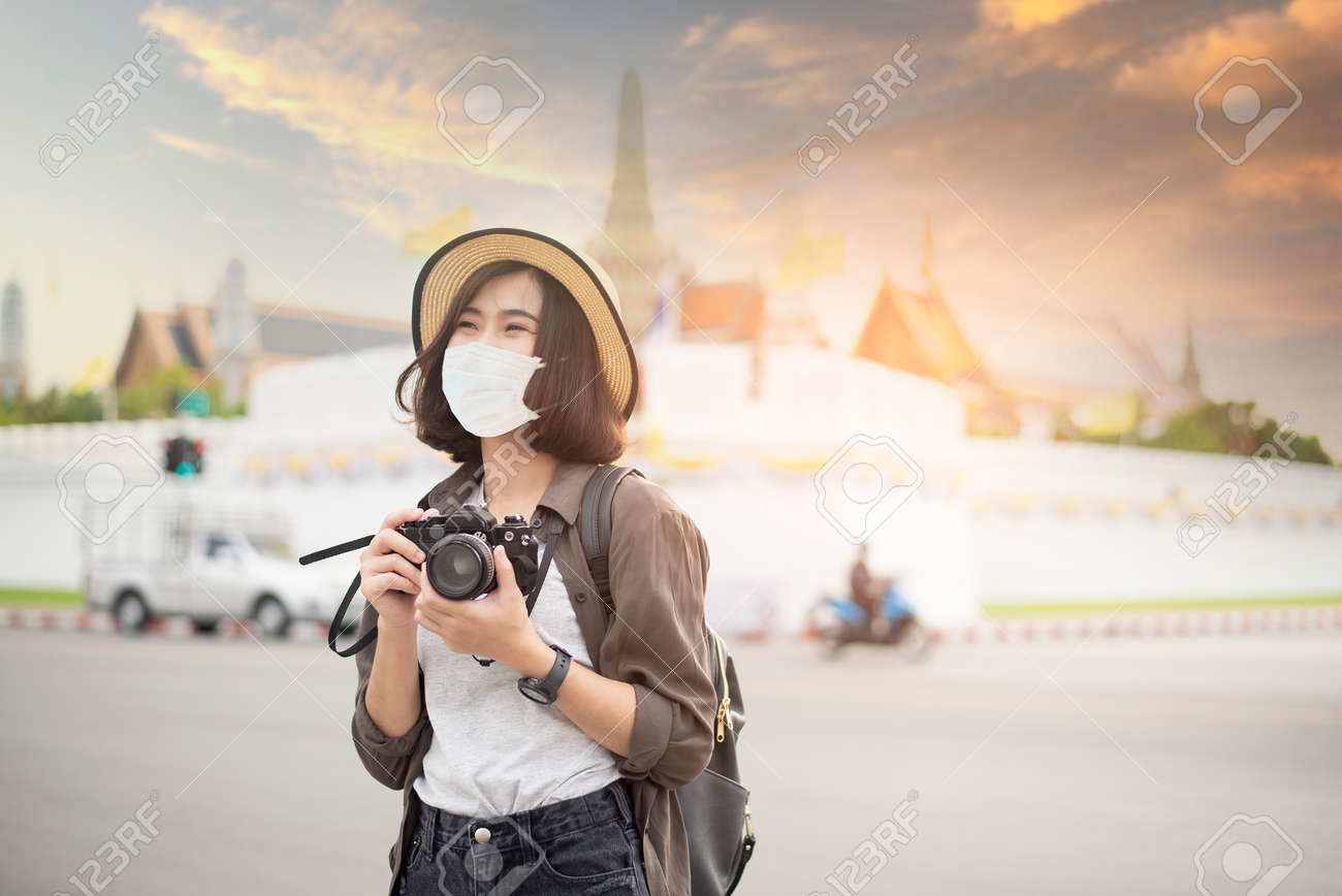 A young pretty Asian woman is wearing protective mask travelling around famous places in Bangkok city , New normal travel, covid-19 protection , safe travels , travel under COVID-19, Post- pandemic travel concept. - 162001340