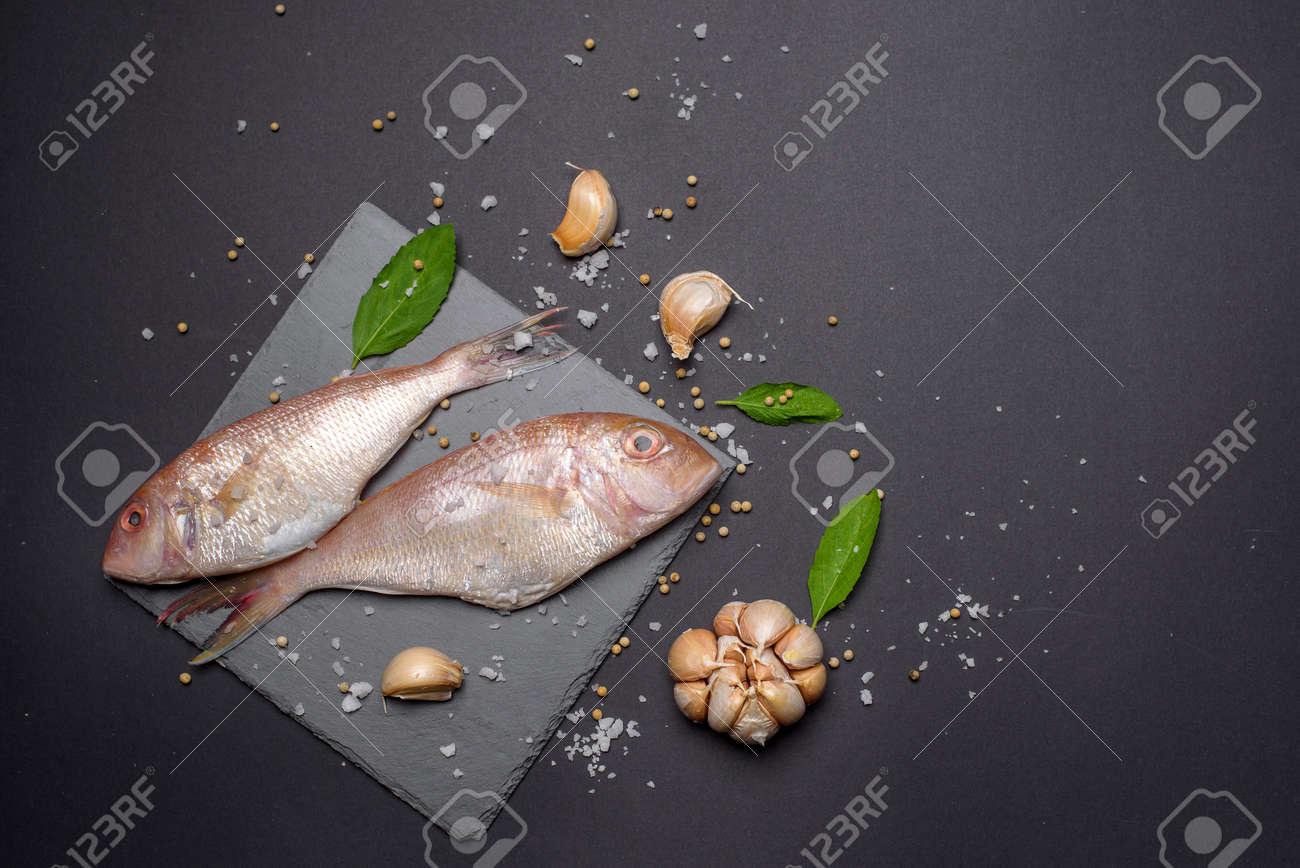 Fresh sea fish flat lay copy space on black background - 168178197