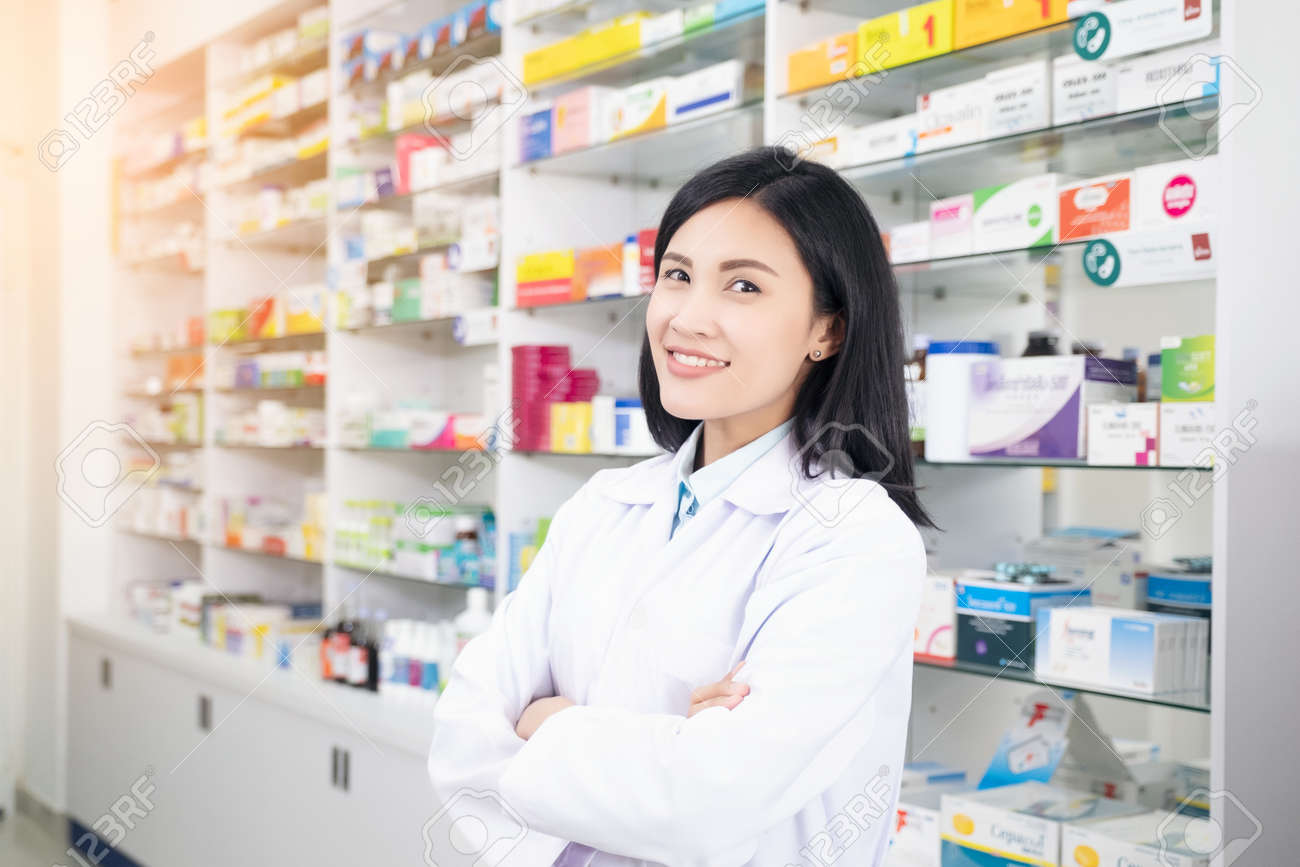 Beautiful smiling young woman pharmacist doing his work in pharmacy. - 123919987