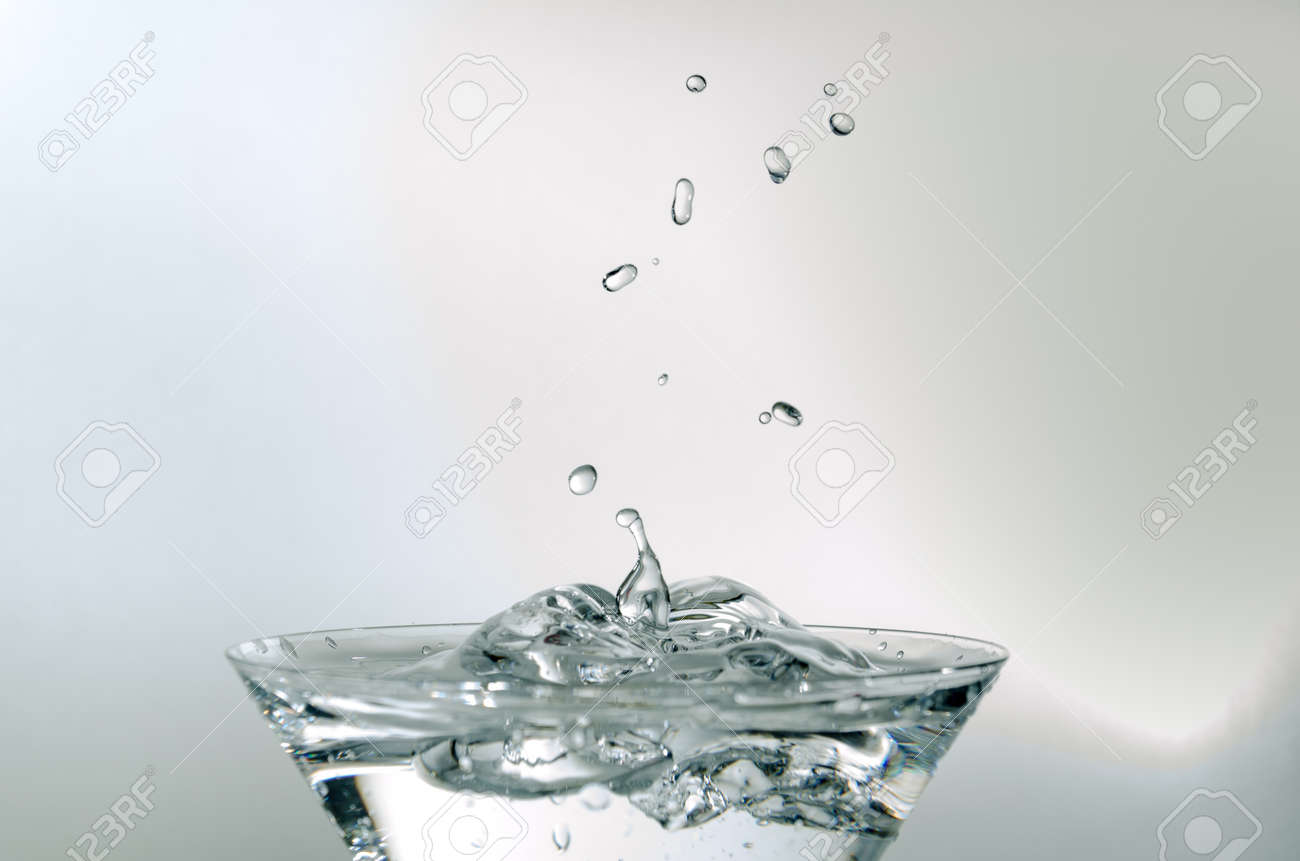 Close-up of water drop falling into a glass on white background - 165324618