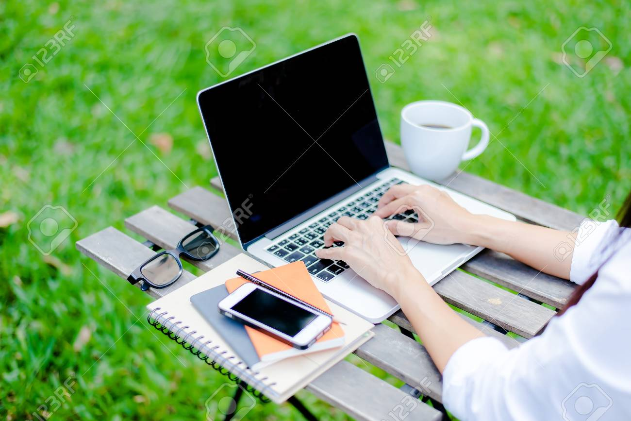 Casual Dressed Man Sitting At Wooden Desk Inside Garden Working On Computer  Pointing
