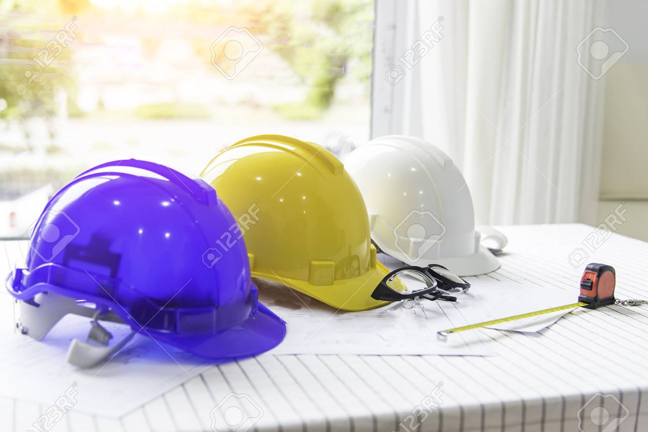The safety helmet and the blueprint on table at construction stock stock photo the safety helmet and the blueprint on table at construction sitesafety helmet whiteblue and yellow for foremanengineerarchitectvisitor malvernweather Images