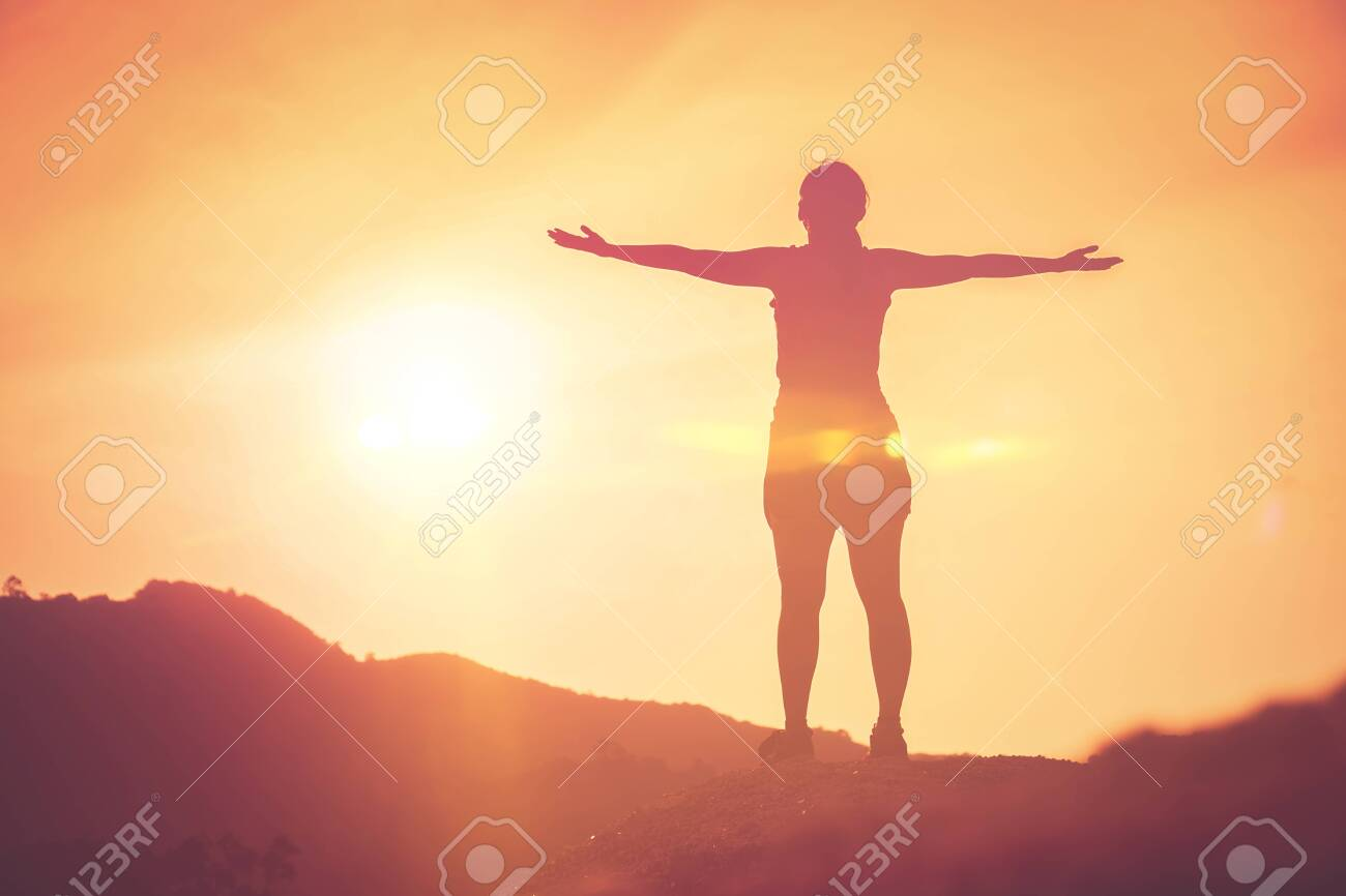 Copy space of silhouette woman raise hand up on top of mountain and sunset sky cloud abstract background. Freedom feel good and travel adventure holiday concept. Vintage tone filter effect color style - 134345451