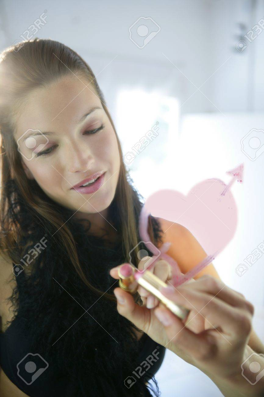 Beautiful woman painting a lipstick red heart on make up mirror Stock Photo - 4128293