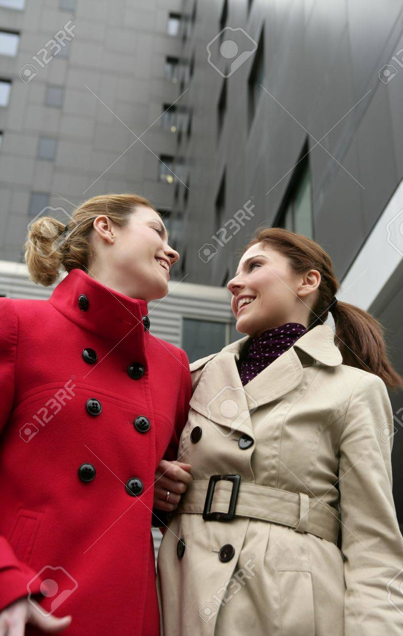 Two Happy Young Women With Winter Coats Black Building Background
