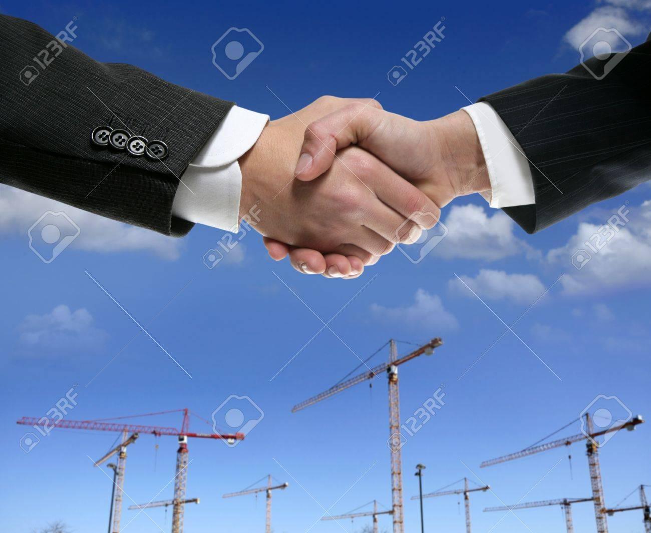Businessmn handshake in construction crane area over blue sky Stock Photo - 4484363