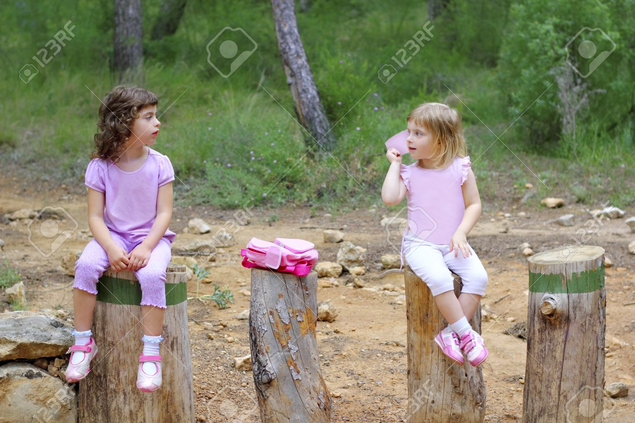 two little girls sit on forest park tree trunks green pine woods Stock Photo - 7357259