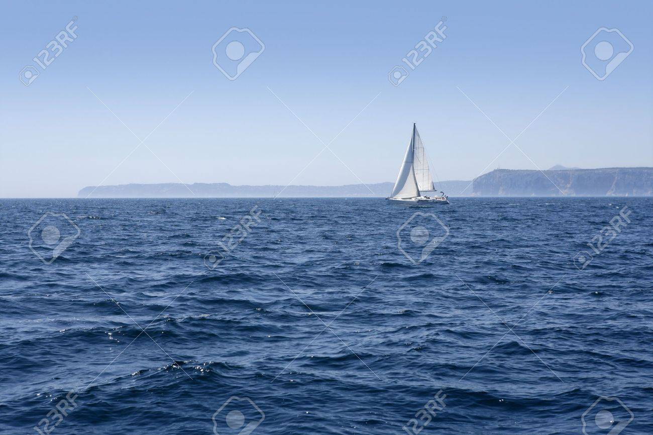 Blue sea with sailboat sailing the ocean surface Stock Photo - 8289613