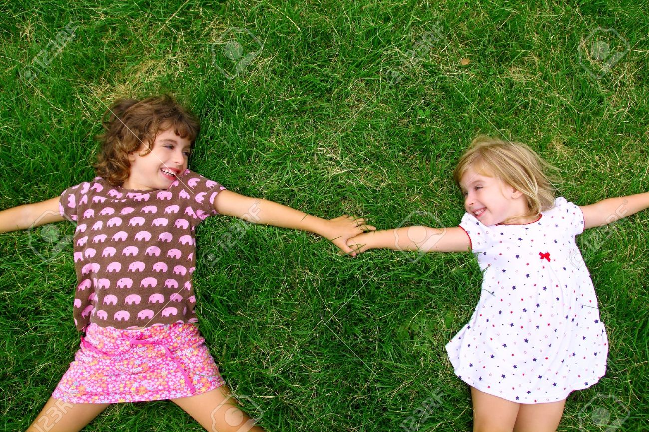 two sister girls lying on meadow green grass like friends playing Stock Photo - 8385074