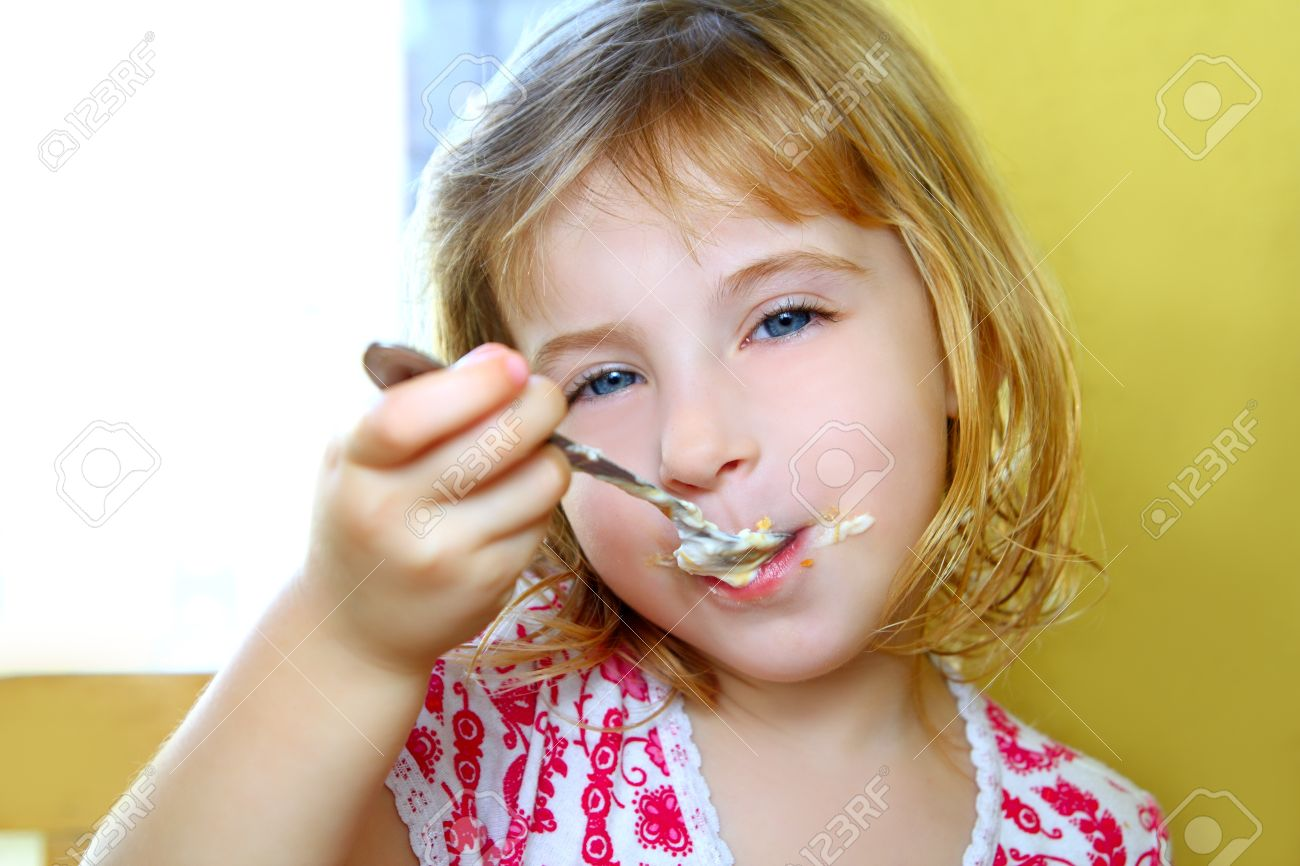 hungry little blond girl spoon eating ice cream pastry dirty mouth Stock Photo - 9030746