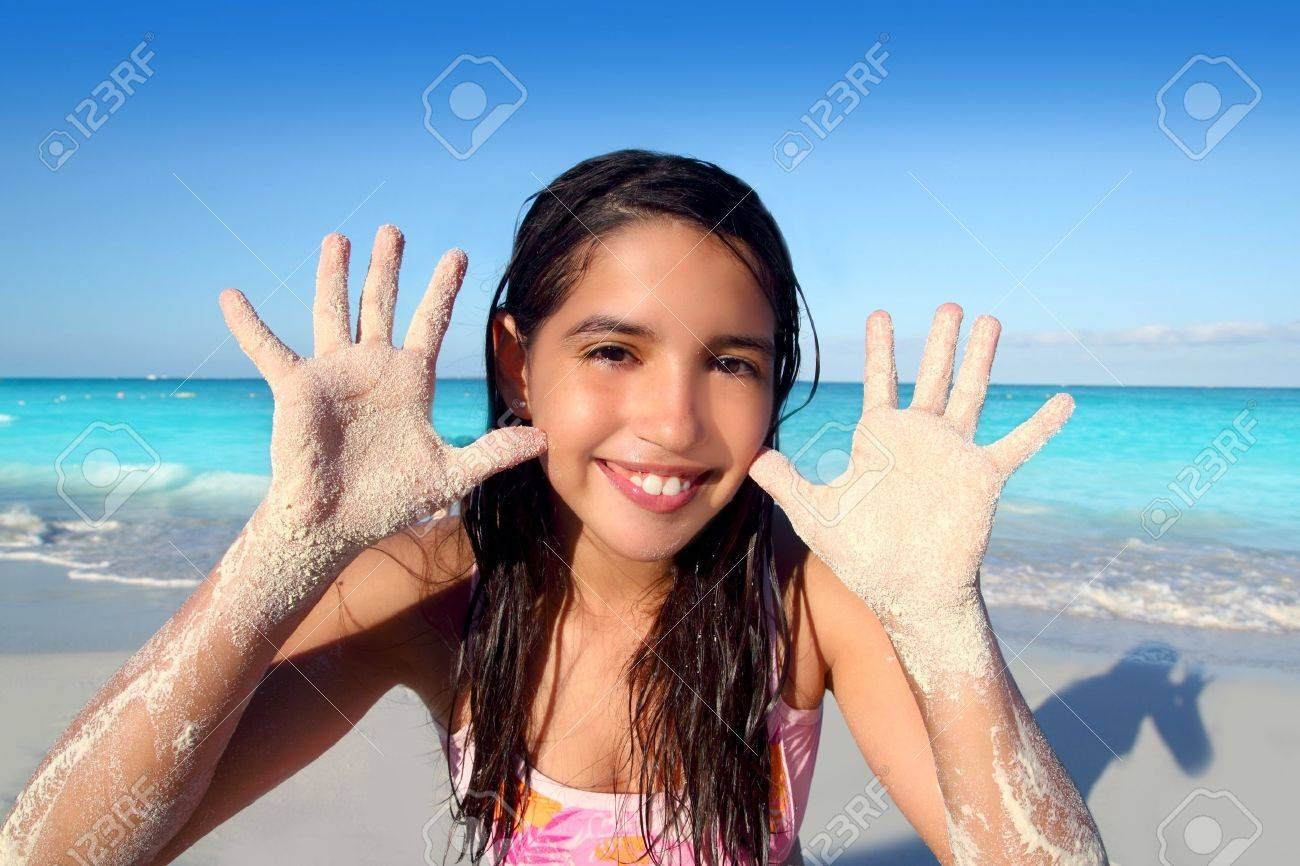latin indian teen girl playing beach showing sandy hands in Caribbean tropical sea Stock Photo - 9607514