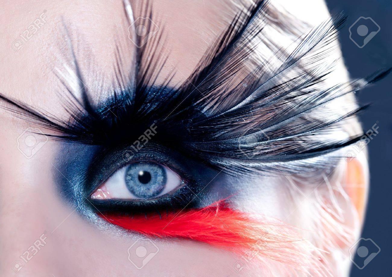 Banque dimages , yeux bleus avec une femme doiseaux de maquillage de mode inspirée de plumes noires et rouges