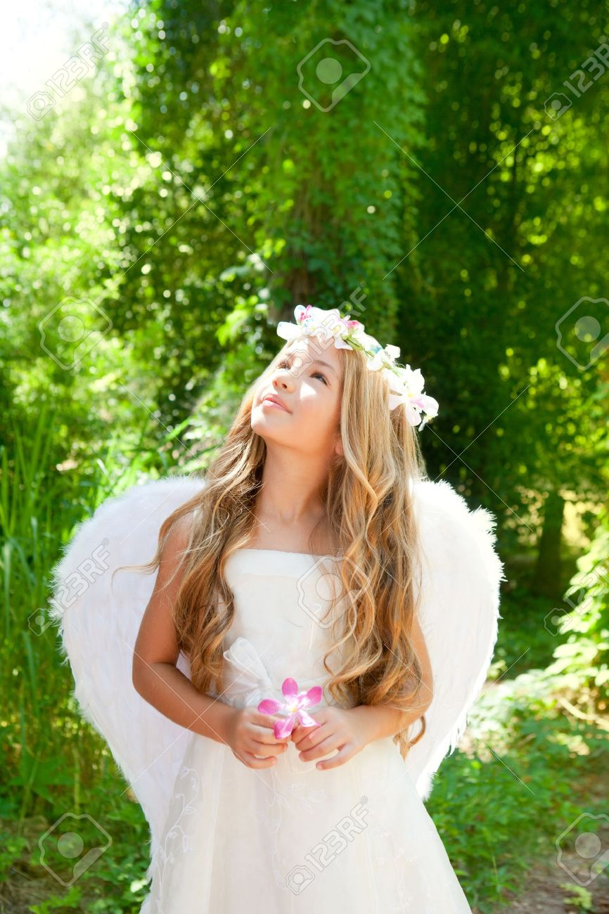 Angel children girl in forest holds flower in hand looking sky Stock Photo - 10214489