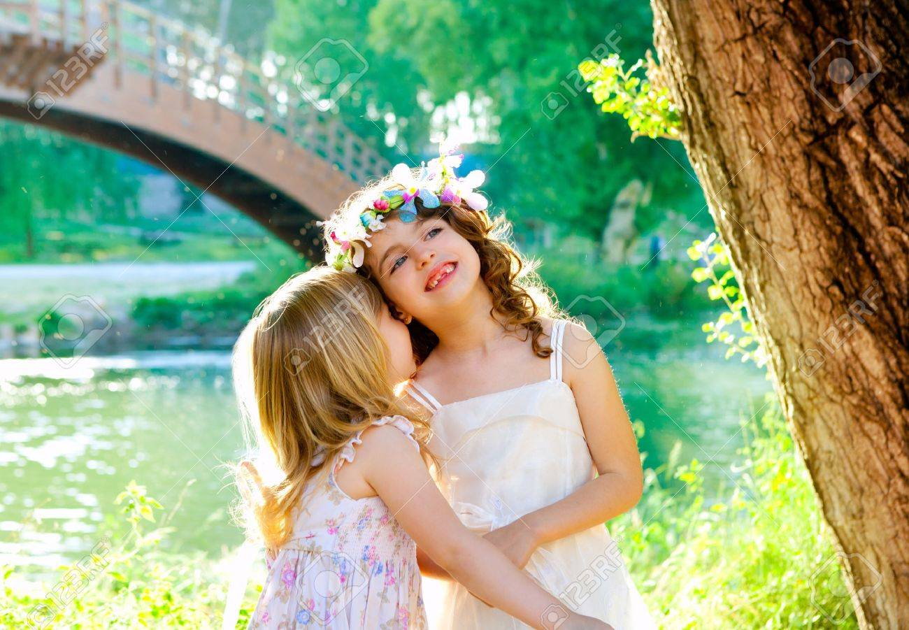 kid girls playing in spring outdoor river park whispering ear Stock Photo - 11149715