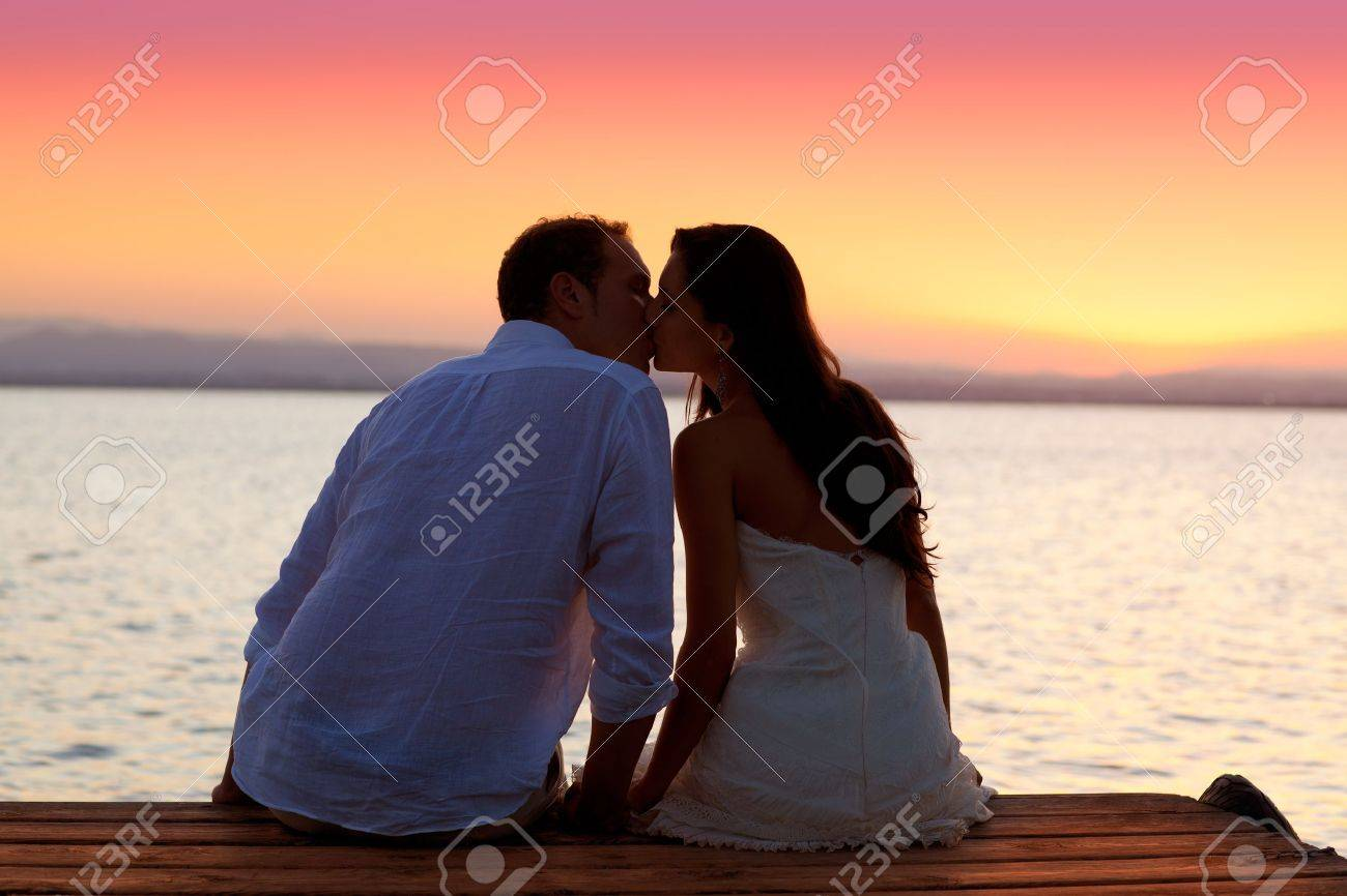 couple kissing at sunset sitting in jetty at orange sea lake Stock Photo - 11149570