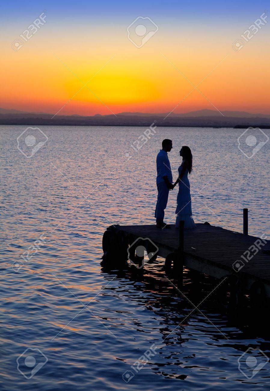 couple in love back light silhouette at lake sunset full length Stock Photo - 11149775