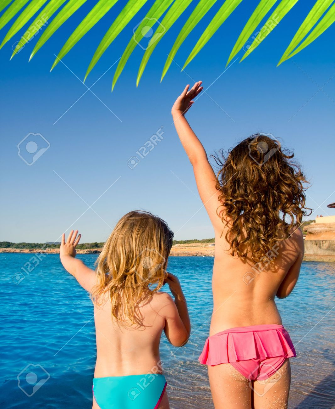 Ibiza Cala Conta beach little girls greeting hand sign saying bye Stock Photo - 11191330