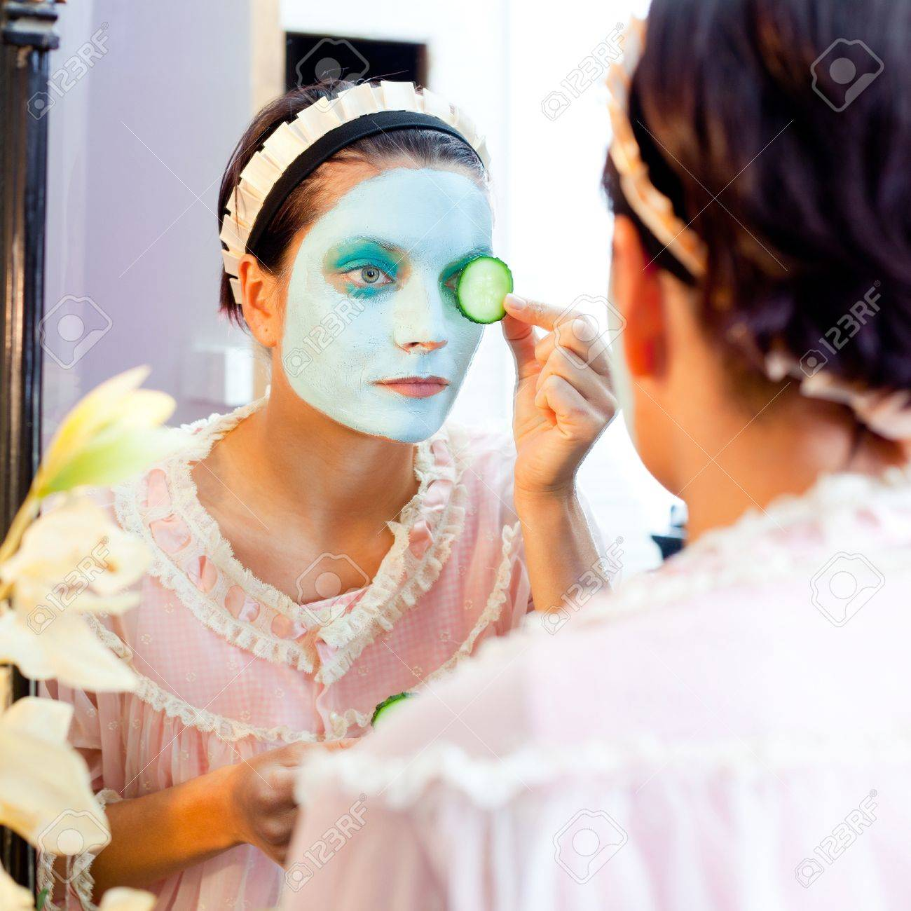 Funny housewife beauty green clay mask and cucumber at the mirror Stock Photo - 12144705