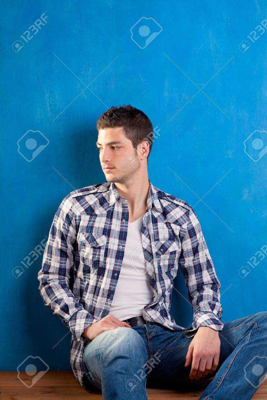 handsome young man with plaid shirt sitting on wood in blue background Stock Photo - 13123940