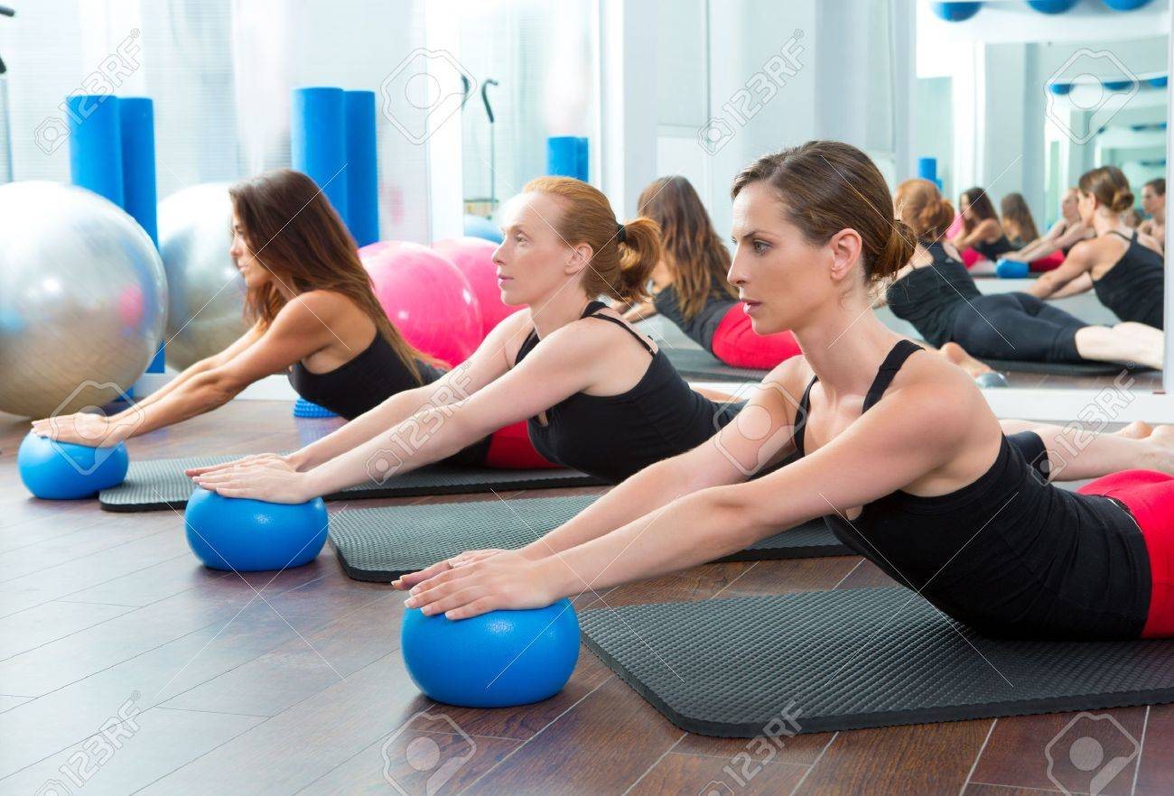 aerobics pilates women with yoga balls in a row on fitness classaerobics pilates women with yoga balls in a row on fitness class stock photo 15444298