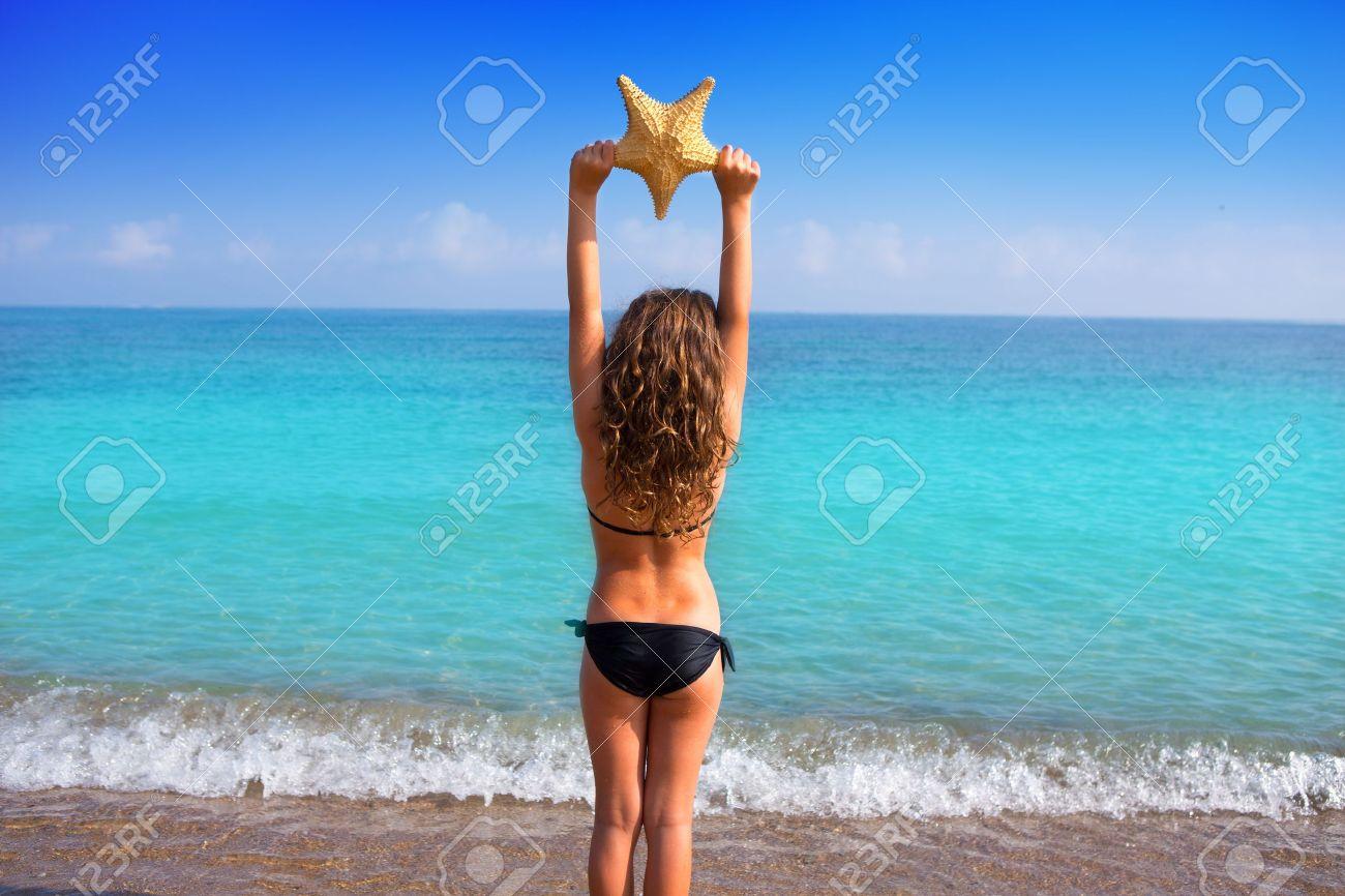Blue Beach Kid Girl With Bikini Holding Starfish Looking Sea In Rear View Stock Photo