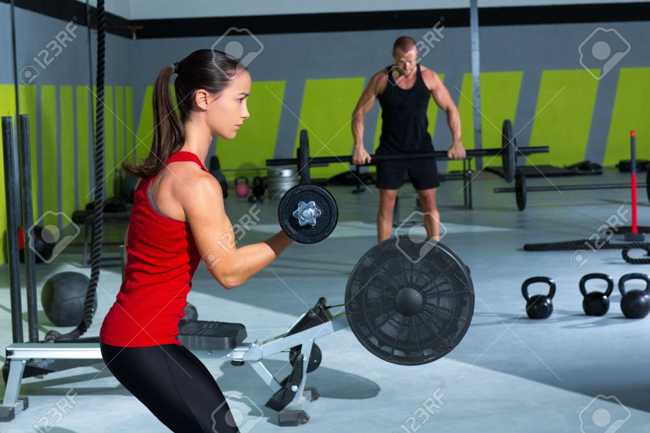 girl dumbbell and man weight lifting bar workout  at crossfit gym Stock Photo - 17050611