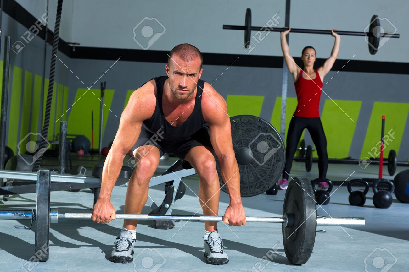 gym man and woman with weight lifting bar workout in crossfit
