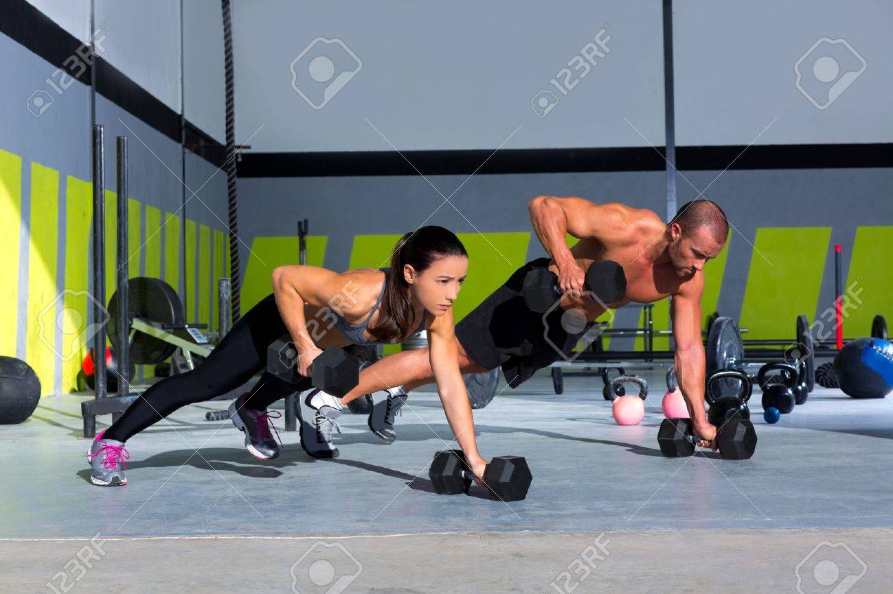 Gym man and woman push-up strength pushup with dumbbell in a crossfit workout Standard-Bild - 17050590