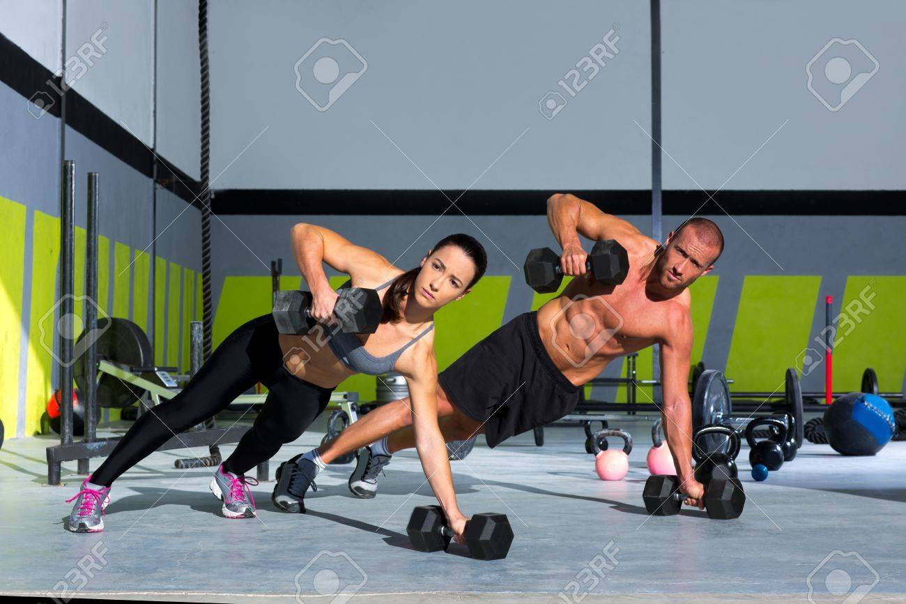 Gym man and woman push-up strength pushup with dumbbell in a crossfit workout Stock Photo - 17050608