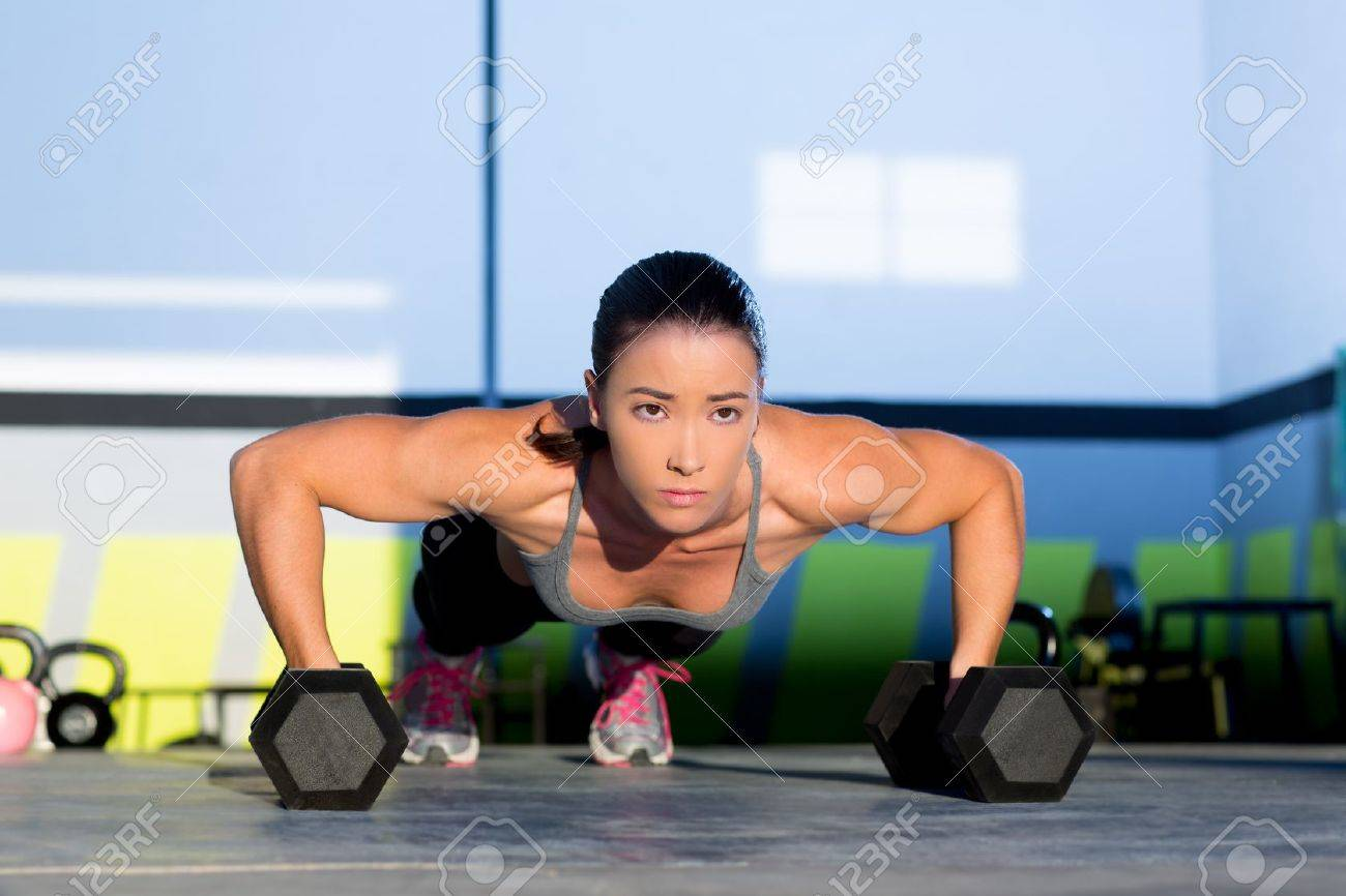 Gym woman push-up strength pushup exercise with dumbbell in a crossfit workout Stock Photo - 17050659
