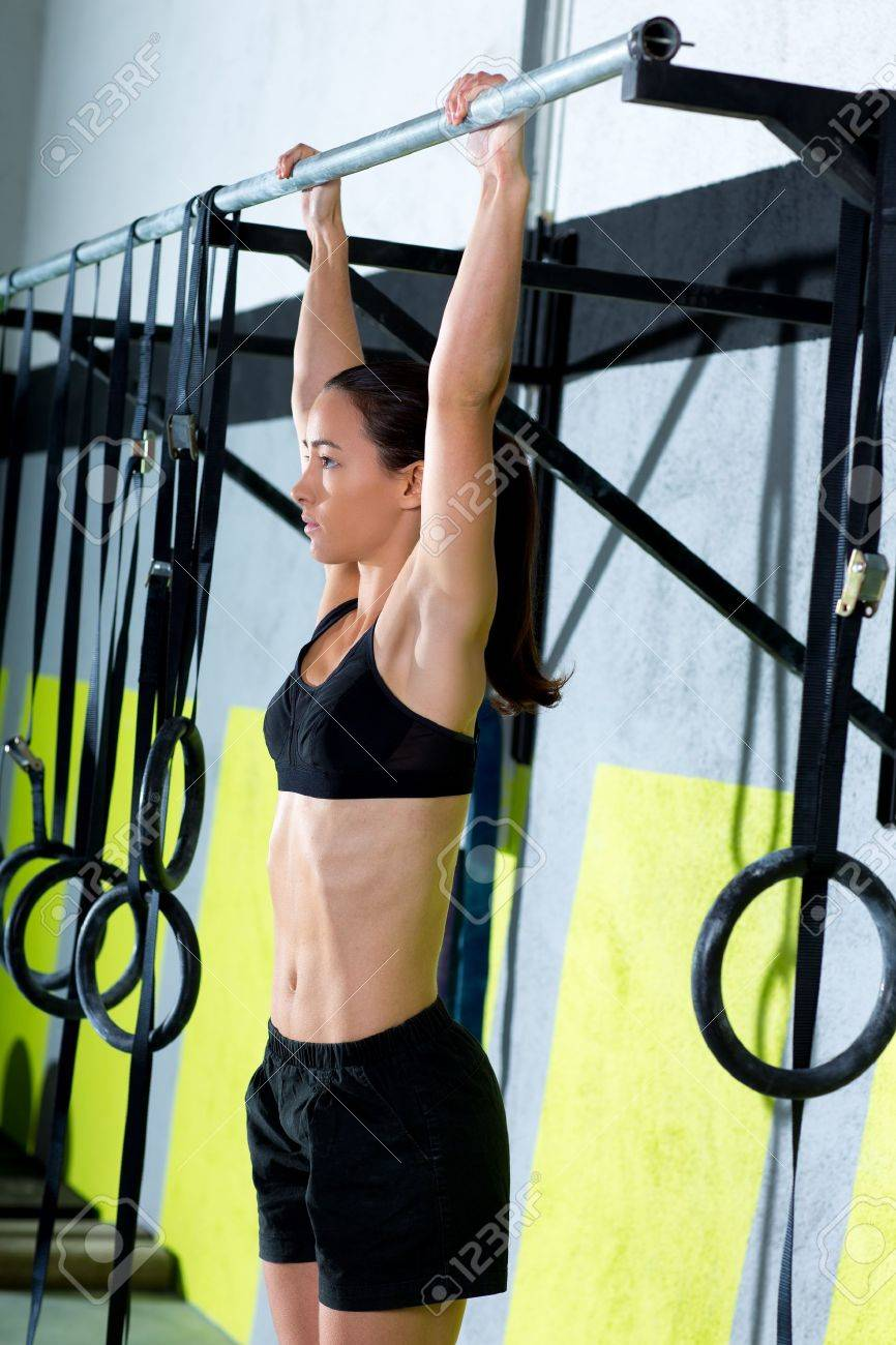 Crossfit toes to bar woman pull-ups 2 bars workout exercise at gym Stock Photo - 17050644