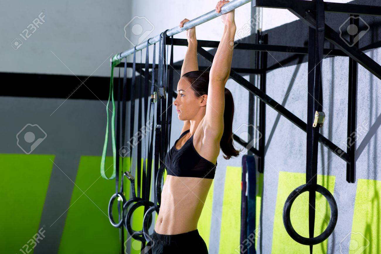 Crossfit toes to bar woman pull-ups 2 bars workout exercise at gym Stock Photo - 17050645